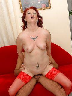 Секс с рыжей зрелкой в красных чулках на красном диване